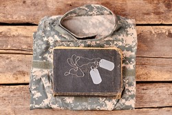 Camouflage army clothes, book, and dog tags on wood. Flay lay, top view.
