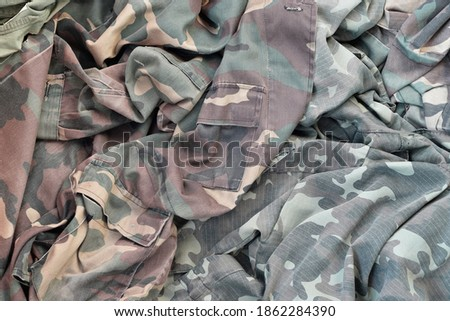 Photo of  Camouflage background texture as backdrop for russian or ussr snipers design projects. Back side of snipers camouflage jacket with many pleats on crumpled fabric