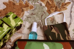 Camouflage cloth mask,hand sanitizer spray inside storage bag with toy jeep. Concept of New Normal for outdoor activities,travel, journey and road trip safety during Covid-19 or Coronavirus pandemic.