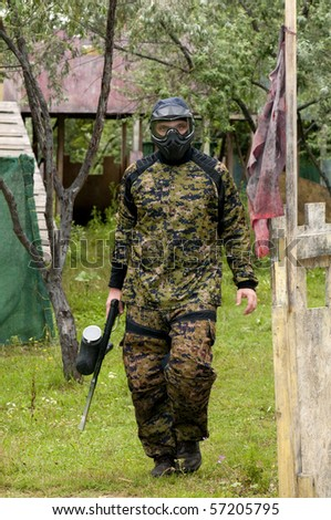 Camouflage dressed paintball player walking on the battle ground