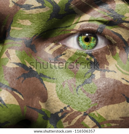 Camouflage painted on a face with green eye to portray military personnel or guerrilla