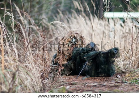 camouflage sniper in the dry grass