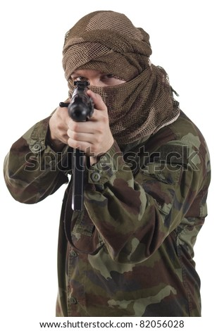 Camouflaged guerrilla soldier with hidden face and a machine gun aiming at camera.