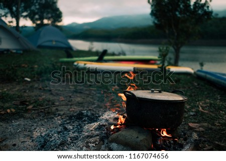 Camp and cooking in field conditions, boiling pot at the campfire on picnic in morning.  Cooking dinner on firewood stove using firewood when going to the wilderness or outdoor activity, camping tent #1167074656