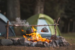 Camp fire and tea pot are foreground and focused, there is a tent in the background and defocused