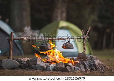 Camp fire and tea pot are foreground and focused, there is a tent in the background and defocused Stock photo ©