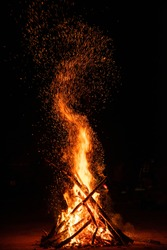 Camp fire in the night. Burning wood at night. Campfire at touristic camp at nature in dark. Flame amd fire sparks on black  background. Hellish fire element. Fuel, power and energy