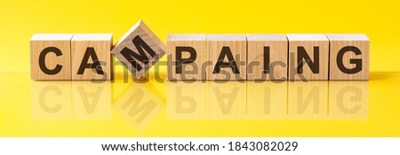 CAMPAING word written on wood block. CAMPAING word is made of wooden building blocks lying on the yellow table. CAMPAING, business concept, yellow background Foto stock ©