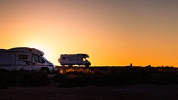 Camper recreational vehicles at sunset on mediterranean coast in Spain. Camping on nature beach. Holidays and travel in motor home.