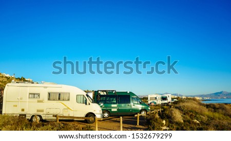 Camper, recreational vehicles on mediterranean coast in Spain. Camping on nature beach. Holidays and travel in motor home.