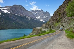 Camper travels alongside St Mary's Lake and mountains in Glacier National Park