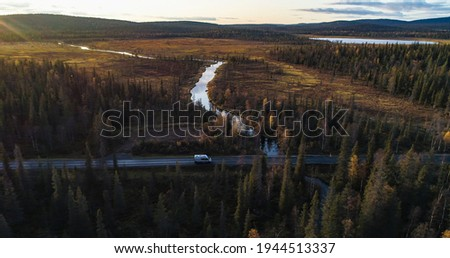Camper van in a autumn forest in Lappland, aerial drone view of a caravan car, driving in middle of foliage trees, on a sunny fall evening, in Lapland Stock foto ©