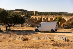 Camper van in Alentejo landscape with abandoned destroyed Ajuda bridge behind, in Portugal