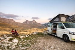 Camper van parked with people sitting looking on over the mountains in the Durmitor National Park in Montenegro at sunset