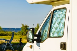 Camper with internal thermal screen blind at window pane camping on nature in summer. Caravan vacation.
