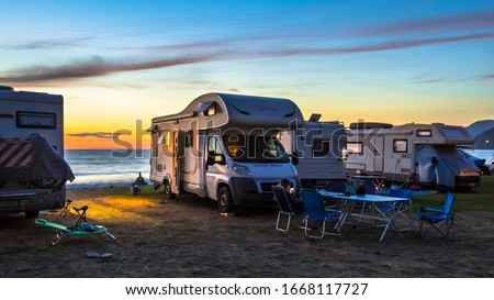 Campers and Motorhomes overlooking sunset in the Mediterranean sea from their campsite on the beach, Corsica, France