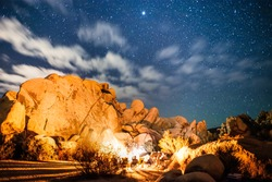 Campers by Fire with Big Rocks and Sky Full of Stars