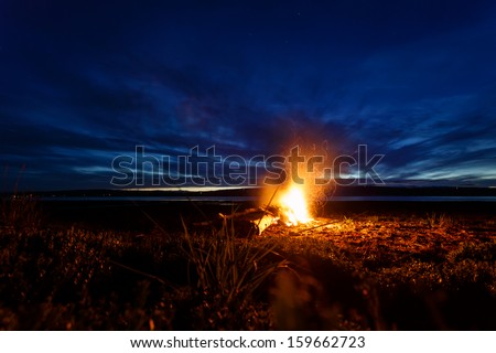 Campfire at twilight on beach in Alaska as sun goes down on summer day. Lights from the City of Seward in the distance.