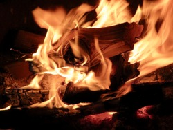 Campfire burning logs in large orange and yellow flames in close up of the wood aflame