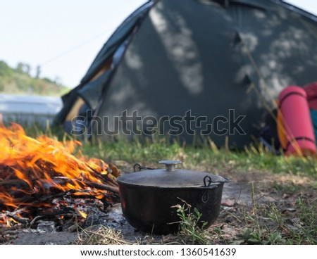 Campfire, cauldron (kettle, pot), tent and sleeping pad near the river. Cooking at the campsite. #1360541639