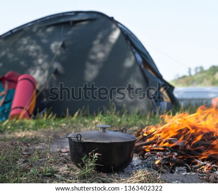 Campfire, cauldron (kettle, pot), tent and sleeping pad near the river. Cooking at the campsite. #1363402322