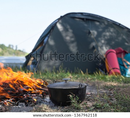 Campfire, cauldron (kettle, pot), tent and sleeping pad near the river. Cooking at the campsite. #1367962118