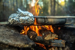Campfire cooking over the coals in the wilderness, baked potato over the fire