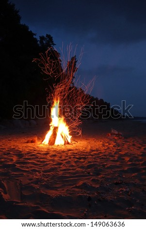 Campfire on the beach in the summer with sparks