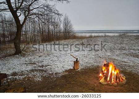 Campfire on the snowy lakeside in twilight
