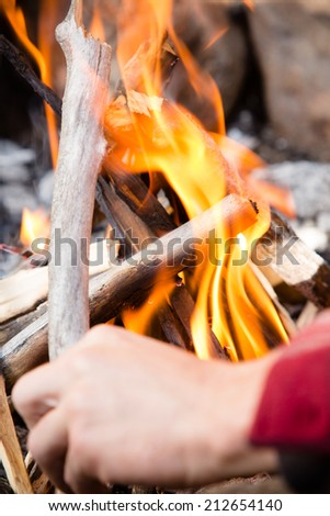 Campfire - This is a shot of a man adjusting a stick on a freshly lit campfire.