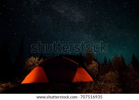 Campground for a starry night. The tent glows under the night sky full of stars. milky way, galaxy.