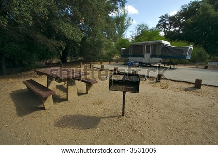 Campground with picnic table, barbecue pit and tent-trailer.