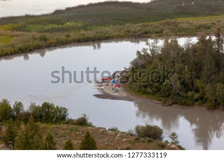 Camping and canoeing in the country, view of a campsite with non recognizable people, canoes and tents on the bank of a curved river in western Canada