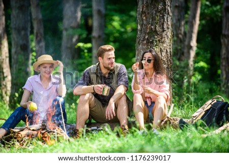 Camping and hiking. Company friends relaxing and having snack picnic nature background. Company hikers relaxing at picnic forest background. Halt for snack during hiking. Relax in nature environment.