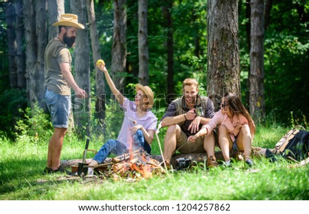 Camping and hiking. Company friends relaxing and having snack picnic nature background. Company hikers relaxing at picnic forest background. Relax in nature environment. Halt for snack during hiking.