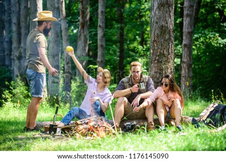 Camping and hiking. Company friends relaxing and having snack picnic nature background. Relax in nature environment. Halt for snack during hiking. Company hikers relaxing at picnic forest background.