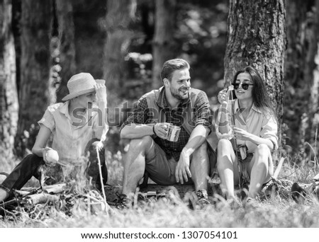 Camping and hiking. Halt for snack during hiking. Company friends relaxing and having snack picnic nature background. Company hikers relaxing at picnic forest background. Relax in nature environment.