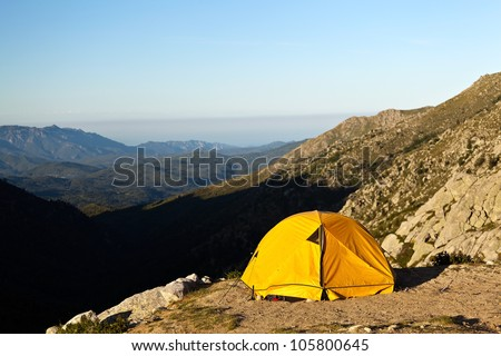 Camping and orange tent in mountains, sunset or sunrise over green valley in Corsica, France.