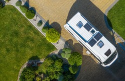 Camping and Tourism Theme. Modern Camper Van with Solar Panels Installed Staying on Cobble Stone Driveway Awaiting New Destination. Aerial View