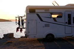 Camping car for relaxing with family on the background of sea sunset, theme of relaxation and nature