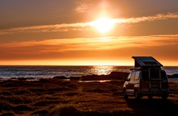 Camping car minivan on the beach at sunset. Beautiful Nature Norway natural landscape Lofoten beach.