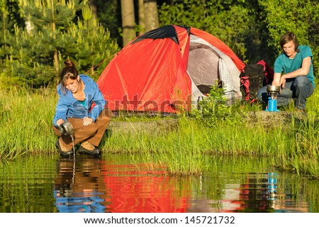 Camping couple heating the supper and washing pot