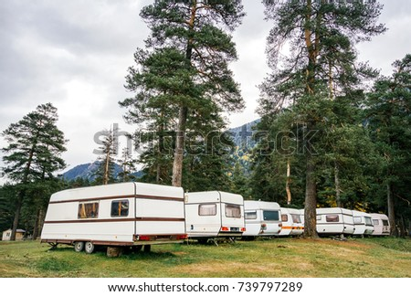 Camping family caravan. Old houses on wheels in the forest camp in the mountains near the river.