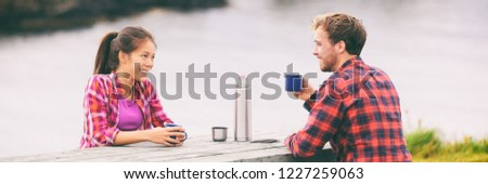 Camping happy couple drinking coffee on morning breakfast table at campsite enjoying summer tourism holidays. Asian tourist woman with man, outdoor.