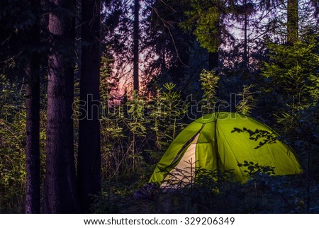Camping in a Forest. Late Evening on a Camp Site. Green Illuminated Tent Between Spruce Trees. Outdoor Lifestyle. #329206349