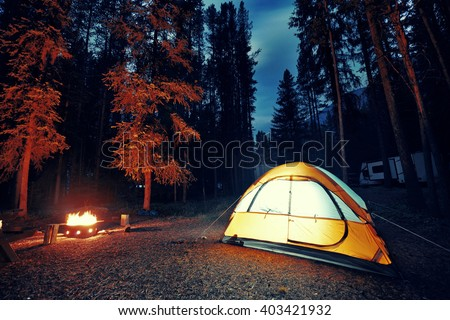Camping in forest with tent light and bonfire in Banff National Park