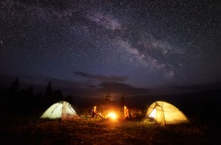 Camping in mountains at night. Bright bonfire burning between two hikers, boy and girl sitting opposite each other near illuminated tents under beautiful evening starry sky and Milky way