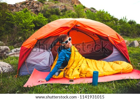 Camping in the forest. A girl is preparing coffee on a geyser coffee machine. A woman sits near a tent in a sleeping bag and prepares coffee against the background of the mountains. #1141931015