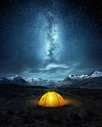 Camping in the wilderness. A pitched tent under the glowing  night sky stars of the milky way with snowy mountains in the background. Nature landscape