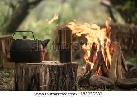camping items by the fire kettle with thermos, travel concept and Hobbies #1188035380